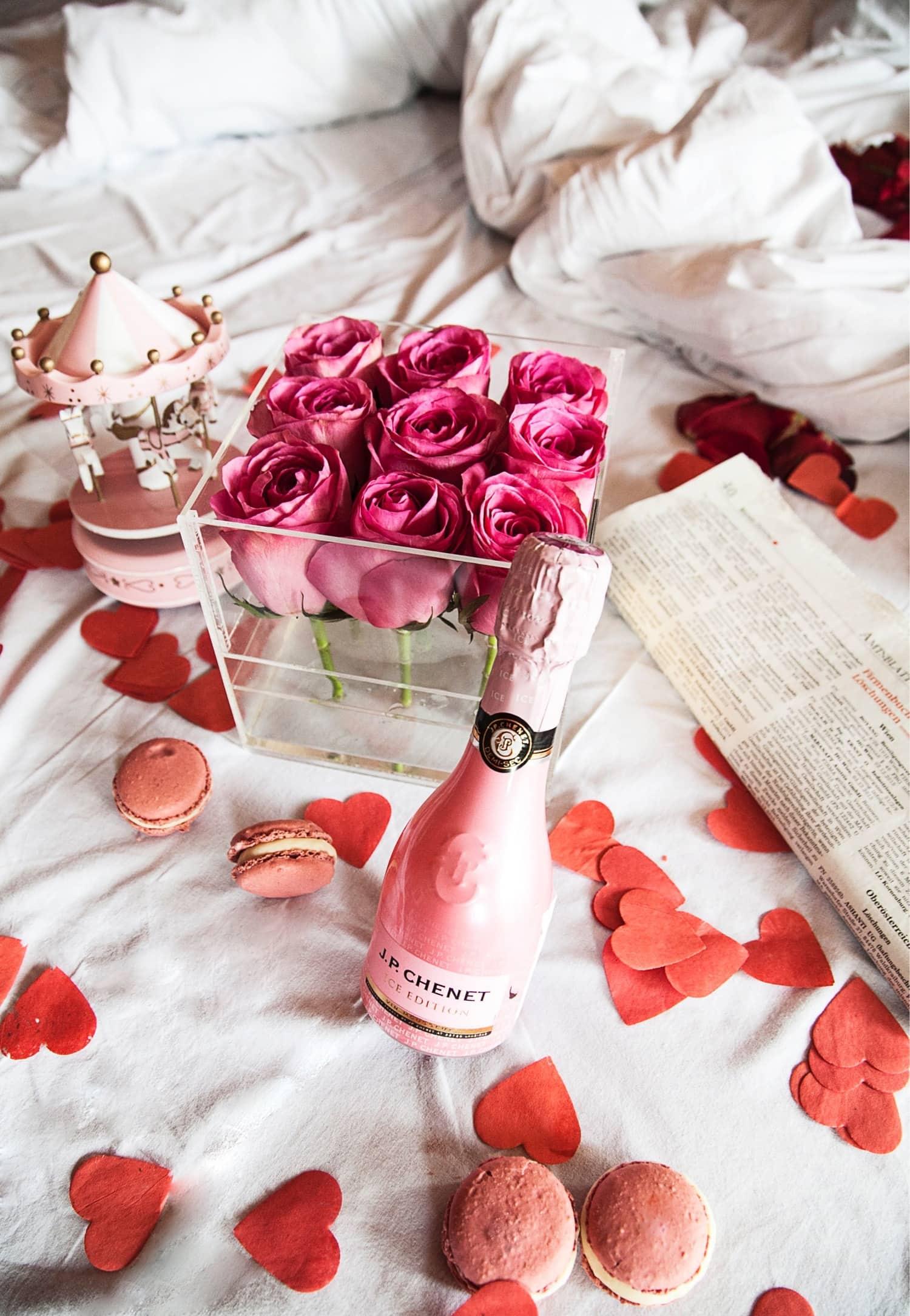 Roze ruze u staklenoj kutiji sa makaronsima i sampanjcem
