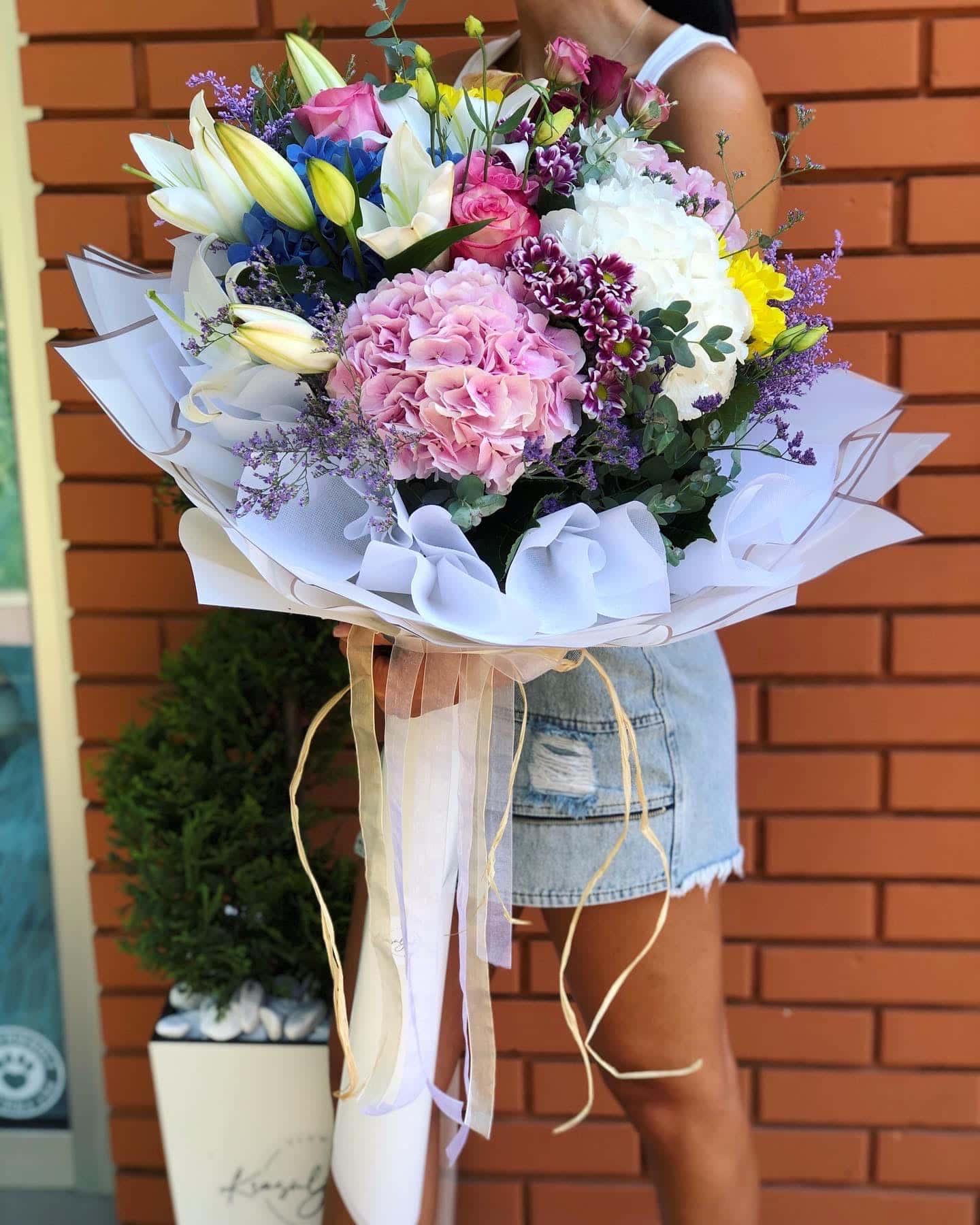Buket cveća - šareno cveće, ukrasno zelenilo. Nežno plavi ukrasni papir